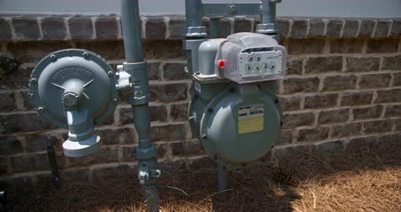 utilidade : Exterior Gas Meter Medium Lowering. lowering shot on a close up of a residential home gas meter on the side Stock Footage