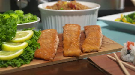 кедр : Salmon Close Up Spin on Table for Party. Camera moves left and spins to focus on salmon on a cedar board. Surrounded by a variety of food for a party