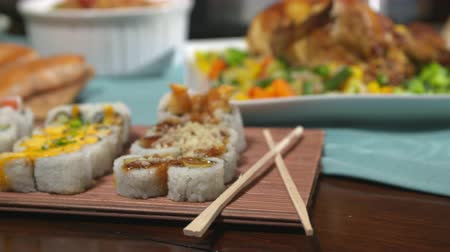 chop up : Sushi Close Up Move Left on a Table Spread. camera moves left over a variety of sushi with chop sticks, surrounded by a variety of other foods for a party