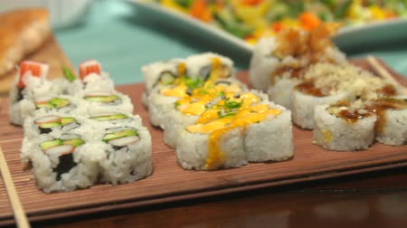 chop up : Sushi Close Up Move Right on a Table Spread. camera moves right over a variety of sushi with chop sticks, surrounded by a variety of other foods for a party