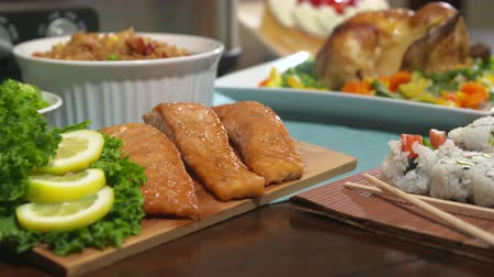 кедр : Chicken Tilt Down to Salmon. camera moves from chicken and racks focus to salmon on a table for a party. Surrounded by other foods