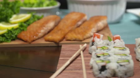 кедр : Sushi Salmon and Chick on Food Spread Spin Tracking Shot. camera moves left on sushi and salmon then spins right to focus on chicken in the background. Party spread of food on the table