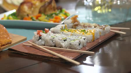 chop up : Table with Food Move Toward Sushi. camera moves toward a variety of sushi on a table with food for a party