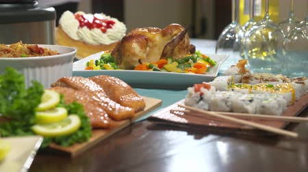 preparado : Table with Food Rack Focus. rack focus from chicken to salmon on table with sushi and wine glasses