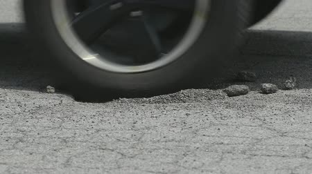 asfalt : Tire Hits Pothole Close Up Slow Motion. a low close up of suv tires hitting a pothole on a road. Driving from right to left