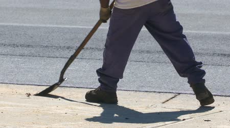 asfalt : Asphalt Worker Scraping Ground with Shovel. A slow motion shot of Pavement Construction workers cleaning an asphalt area before paving