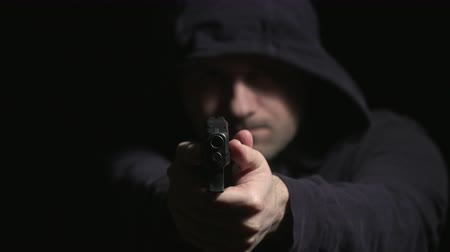 matança : Hooded Man Walks Up and Points Gun . a hooded man walks out of the darkness towards camera, lifts gun and points it directly into the camera and racks focus to the gun Stock Footage