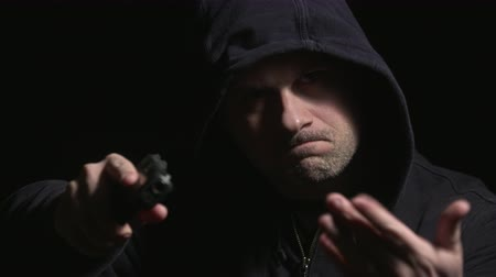 villain : Hooded Man Walks Up and Points Gun Motions Hand Rack Focus. a hooded man walks out of the darkness towards the camera, lifts gun with right hand and motions with other hand to hand something over. Rack focus to gun.