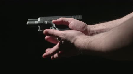 carregamento : Hands Loading a Gun Clip and Unloading Clip and Round. side profile of someone holding a gun and loading a clip. Loads chamber, unloads clip and ejects shell from barrel Vídeos