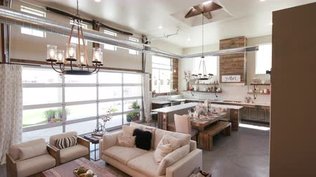 столовая : Modern Open Living Space with Kitchen Lower Right Angle. a lowering shot of a unique modern rustic industrial living open floor plan living space with kitchen and high ceilings Стоковые видеозаписи
