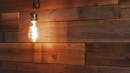low lighting : Lowering on Vintage Modern Wood Wall Light. lowering shot of a reclaimed wood wall with a modern vintage bulb fixture turned on