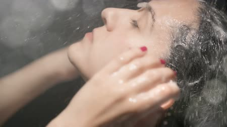 седые волосы : Woman Face Showering Shampoo Rinse Slow Motion. a woman close up of her face rinses shampoo out of her hair with water slow motion with bokeh Стоковые видеозаписи