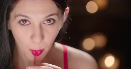 szminka : Woman Sips from a Straw with a Sexy Look. an attractive lady looks up at camera while she sips from a straw in a sexy fashion