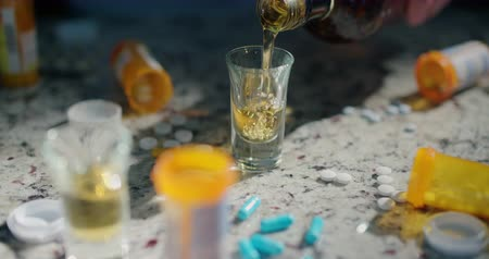 алкоголизм : Variety of Pills and Pouring Glass of Liquor Move Right. a close up of a scene of drugs, pills and liquor pouring in a shot glass on a counter then person grabs pills. Slow motion Стоковые видеозаписи