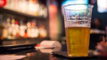 na zdraví : Beer Cup on Bar Grab for a Sip and Place Down. a plastic beer cup is on a bar napkin and a hand picks it up and places it down. Focus on beer cup Dostupné videozáznamy
