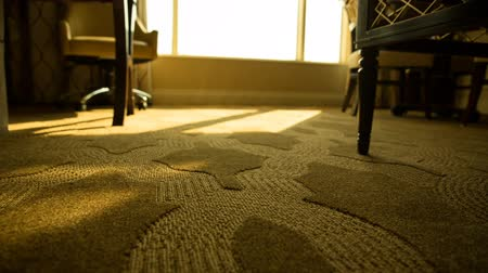 rolety : Hotel Room Low Angle Shades Open Move Left. low angle of hotel room floor as automatic shades and blinds open to reveal morning as view moves left. Orange Tint