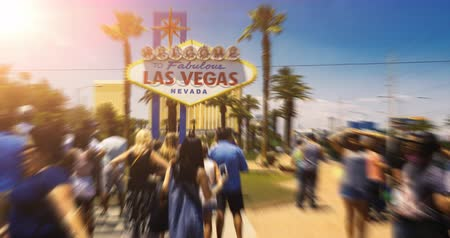 fotky : Las Vegas Welcome Sign People Time-Lapse Sun Flare. tourists take photos in front of the famous Las Vegas welcome sign on a hot summer day. Timelapse with motion blur and sun flare Dostupné videozáznamy