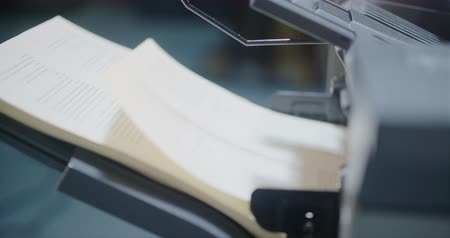 yayıncılık : Printer Side Profile Spinning Out Book Paper Pages. a close up view from right to left of a large printer spitting out paper from the side profile Stok Video