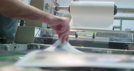 impressão digital : Worker Runs a Laminator Machine. a close up of a worker placing paper into a laminator machine