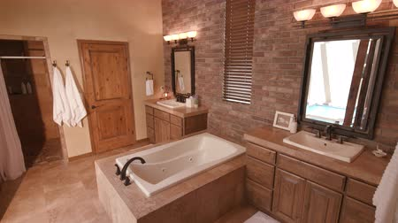tubérculo : Master Bath Double Sink Lower. a lowering shot of a large master bathroom with two sinks and a tub spa in the middle Stock Footage