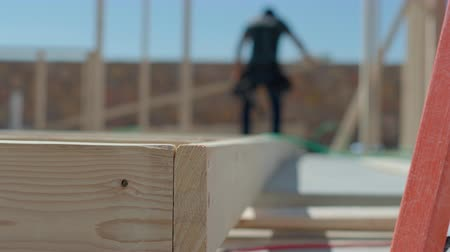 carpintaria : Wood Framing Close Up with Worker. view moves right on a close up on the end of a framed wall on the construction site with a construction worker in the background Stock Footage