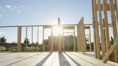 carpintaria : Move Left and Enter Residential Framed Home. view moves left as sun flare wraps around the beams of the new residential home framing wood walls Stock Footage