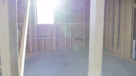 prkna : Move Right on New Home Framing Interior with Sun. view moves lright on the interior of a new home construction build across beams and through a window with sun flare