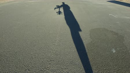 contornos : Shadow View of Person Walking with Camera Gimble System. personal perspective of the shadow of the camera man walking down the street working a camera stabilizer gimble system