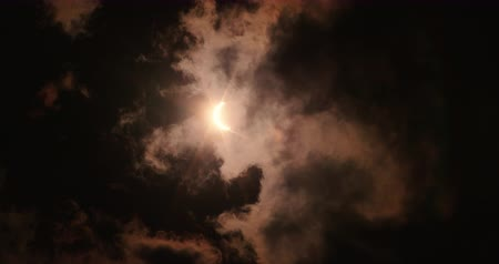 ürpertici : Partial Solar Eclipse with Clouds and Orange Flare. a view looking up at partial solar eclipse with dramatic clouds flying overhead