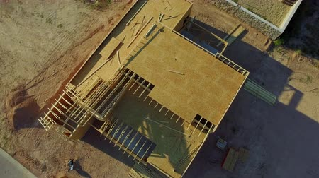 prkna : Residential Home Construction Site Aerial Directly Above. a rising aerial view directly looking down on the top of a home in the middle stages of construction and assembly
