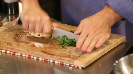 chop up : Cutting Parsley Close Up on Cutting Board. a close up of someone chopping and dicing up parsley in preparation for a meal Stock Footage