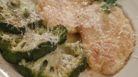göğüs : Move Toward Over Chicken and Broccoli Dish Close Up on Green Mat. view is an extreme close up moving toward over top of a dinner dish of chicken french and broccoli steaks on a dish at a place setting Stok Video
