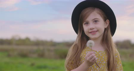 holding onto : Young Girl with Dandelion Smiles with Hat. a close up view of a cute little girl in a black hat holding onto a dandelion smiling in a meadow Stock Footage