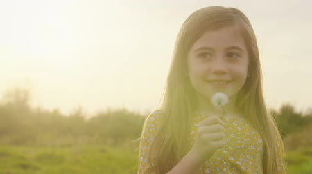 holding onto : Young Girl with Dandelion Smiles at Sunset. a close up view of a cute little girl holding onto a dandelion smiling in a meadow during sunset