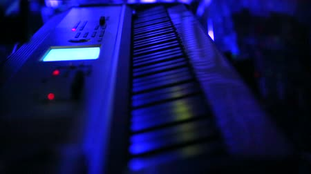 пианино : Music Keyboard Piano on Stage Close Up Rack Focus. a racking focus close up shot of a keyboard on stage with a blue light