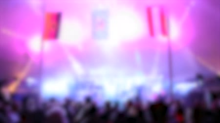 playing band : Band Playing in Tent Tilt Down Blur. a blurred shot of a band and crowd during a performance with light show in a tent
