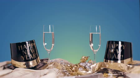 na zdraví : New Years Eve Table Scene with Blue Background. a table scene for New Years Eve with two champagne glasses and hats with ribbon on a blue background