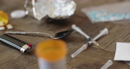 kokaina : Heroin Needles and Pills Close Up Panning Right. view moves right on a close up drug scene with heroin, needles, pills, and a spoon on a table Wideo