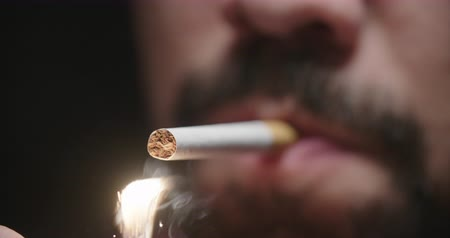 viciado : Close Up Man Lights Cigarette and Smokes. a close up view of a mans lower face with a cigarette and a lighter lights it as he smokes