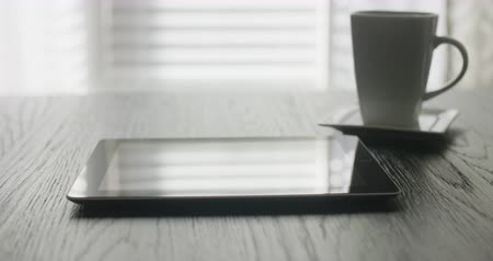 rolety : Tablet Low Angle Move Right on Table. a computer tablet and a coffee mug are on a table with the view moving right