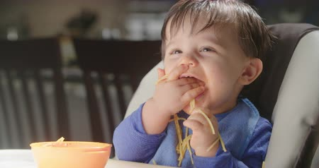 tigela : Baby Eats Handful of Pasta Medium. a medium view of a baby in a highchair grabbing a handful of pasta, eating and smiling. Slow motion