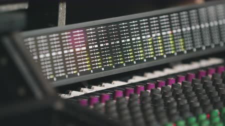 ajustando : Close Up Audio Board to Bouncing Meters. hand held close up of an audio board tilting up to the audio meters bouncing to a recording