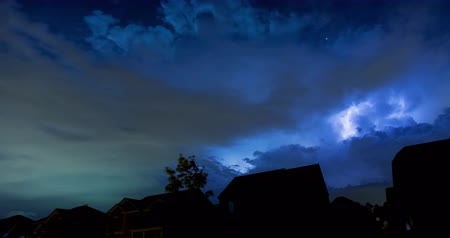 Dramatic Lightning Storm Timelapse in Neighborhood. a time lapse above the rooftops of houses of a dramatic lightning storm rolling by