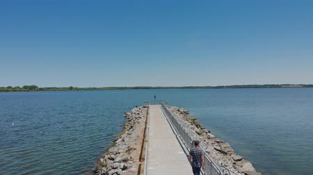 Aerial Pier Toward End and Over Water. an aerial flyover a lake pier while someone walks toward the end