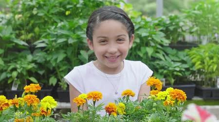 escolha : Young Girl Walks in and Smells Flowers and Smiles. a slow motion shot of a girl in a flower shop smelling flowers and smiling at camera