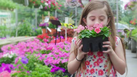 única flor : Young Girl Chooses Flower and Smells. a slow motion view of a girl walking down a line of flowers choosing some to smell and smile at camera