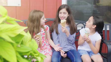 Girls on Bench Eating Ice Cream. a slow motion move right on three girls eating ice cream on a bench talking Vídeos