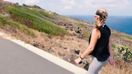 Girl Walking Along Ocean Trail Looking Out. a rising shot of a woman walking on the makapuu trail in Hawaii looking out Dostupné videozáznamy