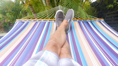 Hammock Swing Point of View Tlit Down. a slow motion personal point of view of a male swinging on a hammock, tilt down from palm trees to legs on hammock Dostupné videozáznamy