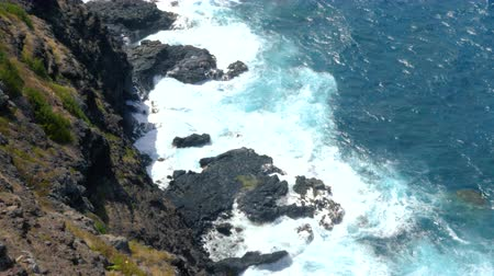 Above View of Ocean Crashing Against Rocks. an aerial view above an ocean shoreline with waves crashing against rocks Dostupné videozáznamy